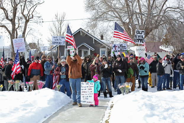 BJ Soper with the TK TK stands with other protestors outside the Hammond home protesting Dwight Hammond's imprisonment for burning 127 acres of BLM land.  Patriots gathered in the Safeway parking lot in Burns, Oregon in Harney County to protest the imprisonment of the Hammonds who burned 127 acres in 2001. After the protest, some of the group, led by Ammon Bundy and the other Bundy brothers went to Melhuer National Wildlife Refuge and took control of the headquarters to take a stance against the tyranny of the federal government.