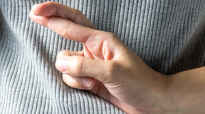 Close up of crossed fingers behind a woman back