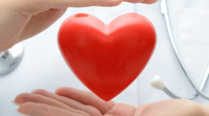 Doctor holding heart, HEALTH CARE