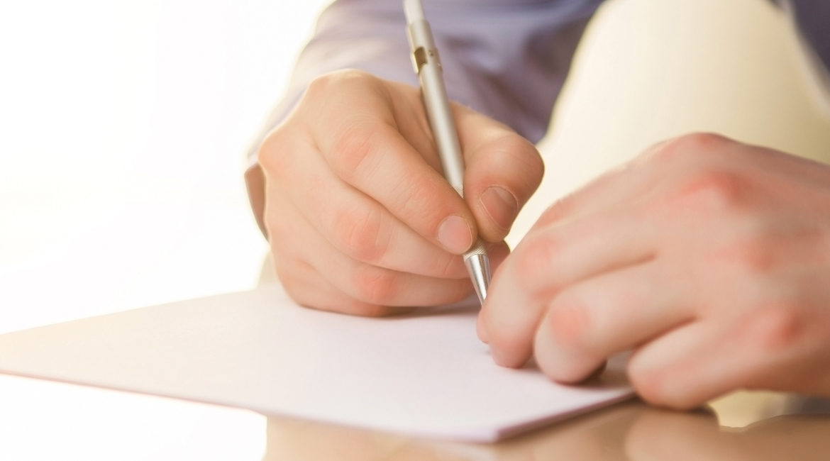 The male hands with a pen and the cup